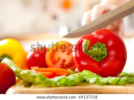 Woman's hands cutting tomato bell pepper, behind fresh vegetables.