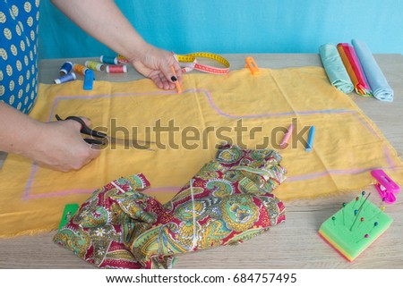 woman's hands drawing a pattern on bright yellow material at her workplace in a tailor shop #684757495