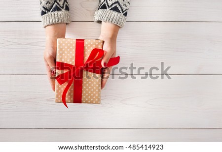Woman\'s hands give wrapped christmas or other holiday handmade present in paper with red ribbon. Present box, decoration of gift on white wooden table, top view with copy space