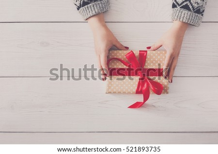Woman\'s hands give wrapped christmas or other holiday handmade present in paper with red ribbon. Present box, decoration of gift on white wooden table with copy space