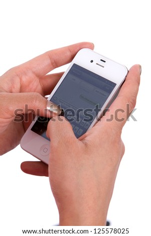 Woman's hands hold a cell phone while texting a message.
