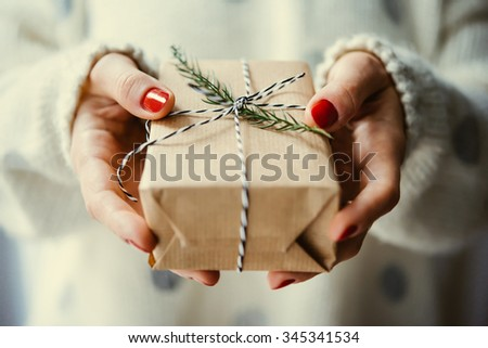 Woman\'s hands hold christmas or new year decorated gift box. Toned picture