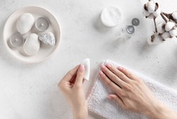 woman's hands holding a cotton pad and removing pink nail polish. hand care, manicure process. white concrete background, top view.