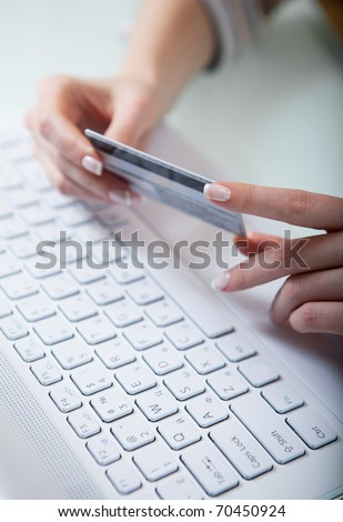 Woman's hands holding a credit card above a keyboard getting ready to enter data