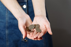 Woman's hands holding a heap of coins background, top view, with copy space