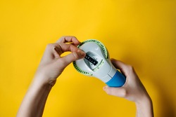 Woman's hands holding a label maker with Hello word typed, on bright yellow background.