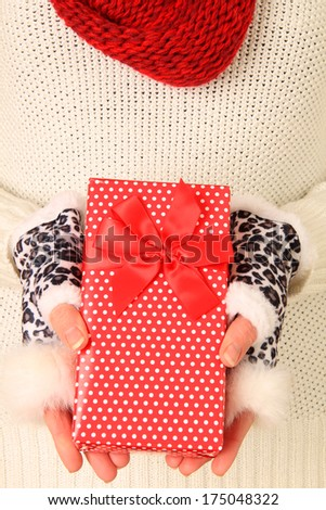 Woman's hands holding a pretty wrapped present.