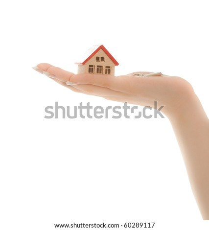 Woman's hands holding a toy house and keys isolated