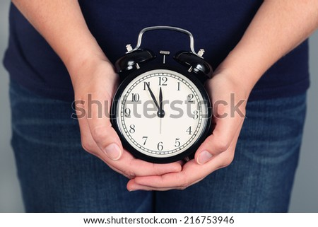 Woman\'s hands holding and showing alarm clock. Five minutes before deadline.