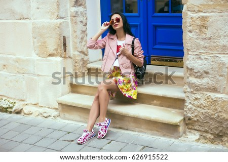 Woman's hands holding beige trendy clutch bag in front of the old city street over wall in summer time outside in the streets. Fashion accessories. Street style summer spring photo,floral sneakers #626915522