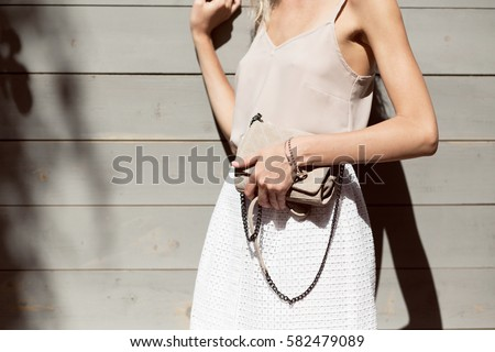 Woman's hands holding beige trendy clutch in front of the wooden wall in summer time outside in the streets. Fashion accessories. Streetstyle summer spring photo #582479089