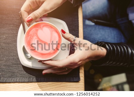Woman's hands holding cup of cappuccino on wooden table. Living Coral colored picture. Beverage concept of color of the year 2019. Top view, flat lay, copyspace for text