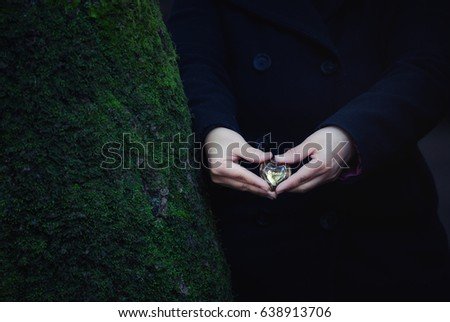 Woman's hands holding gold glass heart inscribed with Love message against moss-covered tree, grainy film, nostalgic, cross-processed #638913706