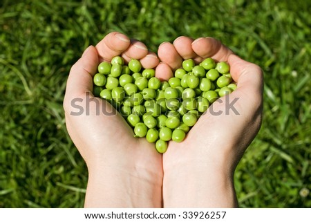 Woman's hands holding green peas, heart shaped
