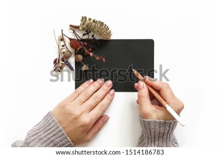 Woman's hands holding pencil. Black sheet of paper decorated with autumn flowers composition. Flat lay photo #1514186783