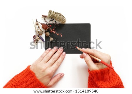 Woman's hands holding pencil. Red sweater. Black sheet of paper decorated with autumn flowers composition. Flat lay photo #1514189540