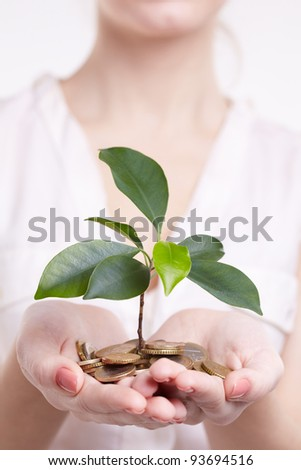 woman's hands holding plant sprouting from a handful of coins