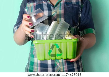 Woman's hands holding recyclable garbage - plastic containers with recycling symbol on it. Recycling, environment and ecology concept.