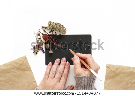 Woman's hands holding white pencil. Black sheet of paper decorated with autumn flowers composition. Craft envelopes. Flat lay photo #1514494877