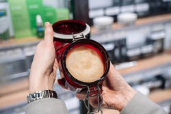 Woman's hands in a cosmetics store is testing hand cream in a large red jar.