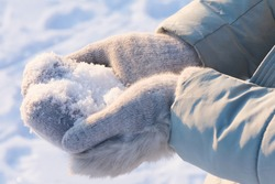 Woman's hands in gray warm mittens holding fresh snow outdoors on a frosty sunny day. Concept of winter holidays, Christmas and new year. Loose snow on mittens.