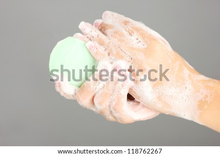 Woman's hands in soapsuds, on gray background close-up - stock photo