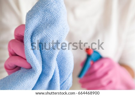 Woman's hands in the rubber protective gloves holding a chemical spray bottle and blue microfiber rag. Housewife cleaning house. Early spring cleaning or regular clean up. #664468900