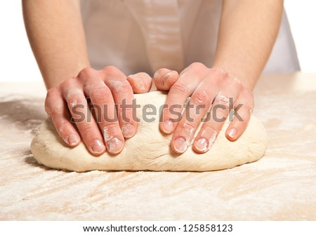 Woman's hands knead dough on wooden table