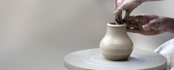 Woman's hands making ceramic cup on potter's wheel