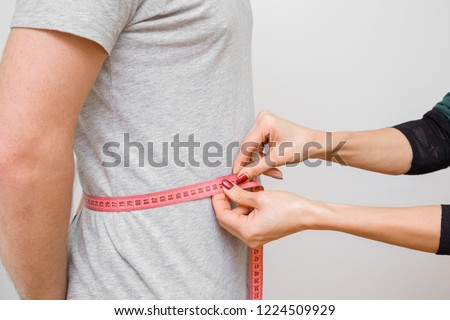 Woman's hands measuring young, slim man's waist with pink measuring tape. Part of body on gray background. Right size. Closeup. Side view. #1224509929