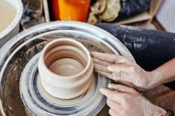 Woman's hands molding clay. Potter making ceramic pot in pottery workshop