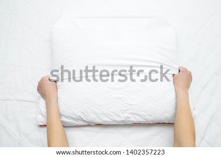 Woman's hands on mattress surface changing white cotton cover on pillow. Regular bed linen change. Closeup. Point of view shot. #1402357223