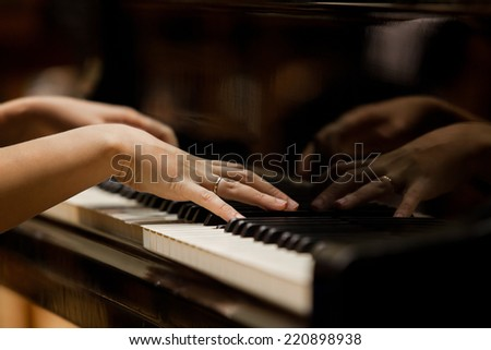 Woman\'s hands on the keyboard of the piano closeup