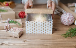 Woman s hands open shine light Christmas gift with snow ball, close up. Unprepared presents on wooden background with decor elements and items, top view. New year DIY packing Concept