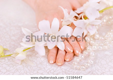 woman's hands, pearl beads and white orchid - stock photo