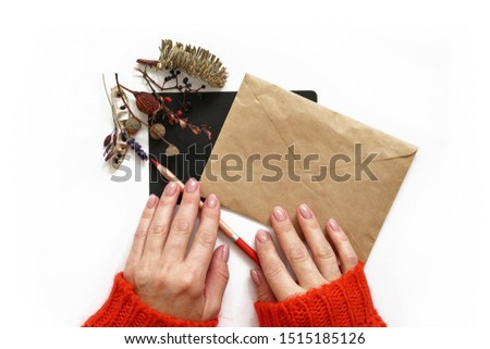 Woman's hands pencil paper and envelope . Red sweater. Black sheet of paper decorated with autumn flowers composition. Flat lay photo #1515185126