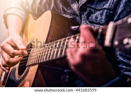 woman\'s hands playing acoustic guitar, close up