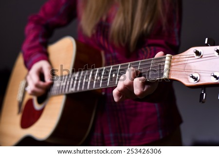 woman\'s hands playing acoustic guitar, close up. Playing acoustic guitar girl or woman with long hair by fingers. finger position on the chord. selective focus image