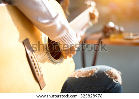 woman\'s hands playing acoustic guitar, close up, soft and select focus