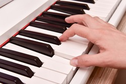 Woman's hands playing electronic digital piano at home. The woman is professional pianist arranging music using piano electronic keyboards. Musician practicing keyboard composing music.