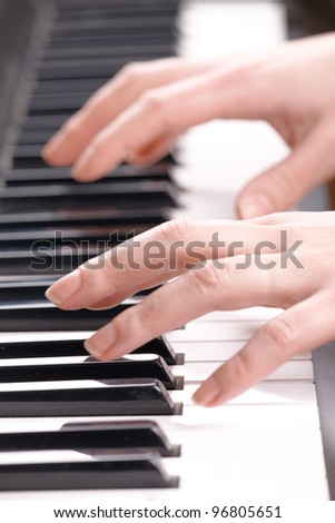 Woman's hands playing music on the piano - stock photo
