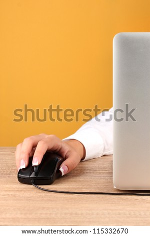 woman's hands pushing keys of pc mouse, on yellow background close-up