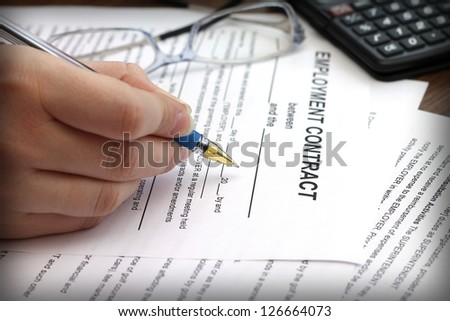 woman's hands signing an employment contract, close-up