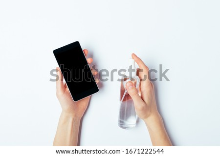 Woman's hands spray disinfectant on mobile phone to clean and protect against viruses, top view on white table.
