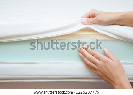 Woman\'s hands touching different layers of new mattress. Checking hardness and softness. Choice of the best type and quality. Front view. Close up.