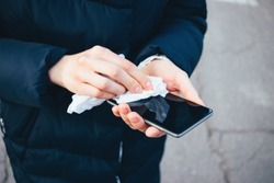 Woman's hands wipe smartphone screen with disinfectant cloth. Close-up woman cleans her mobile phone standing on city street.