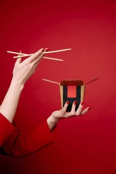 Woman's hands with chinese food in the box and wooden sticks on red background. Noodles and rise. Minimalism. Red clothes. Beige skin. Advertisement. Delivery.  East culture. Asian kitchen.