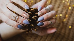 Woman's hands with colorful pattern on the nails. 2021 colors trend. Top view. Place for text. Cozy winter design.
