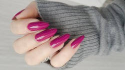 Woman's hands with long nails and pink fuchsia bottle manicure with nail polish
