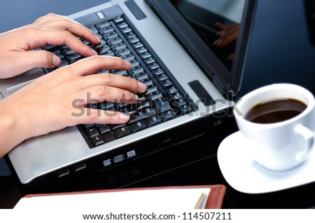 Woman's hands working on notebook keyboard at the desk and coffee